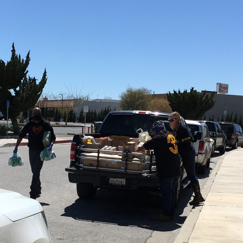 Two people stand by a pickup truck loaded with boxes of supplies. A third person approaches the truck with more supplies in bags.