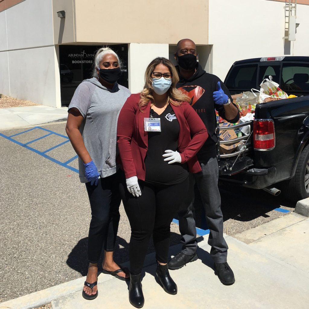 Three people wearing face masks pose next to a pickup truck filled with boxes of supplies.