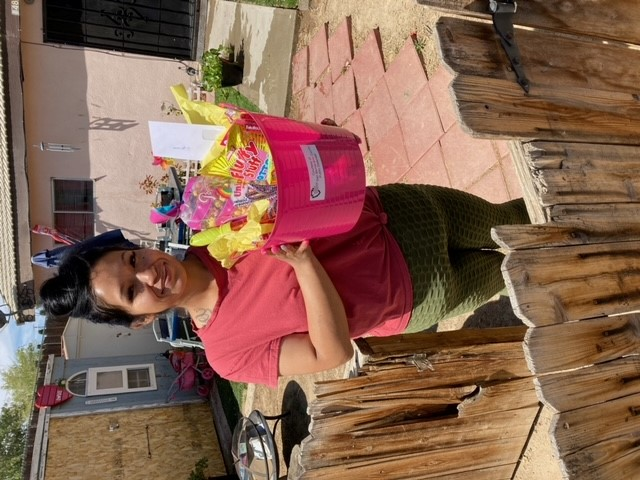 A woman poses behind a wooden gate with a bright pink basket filled with treats.