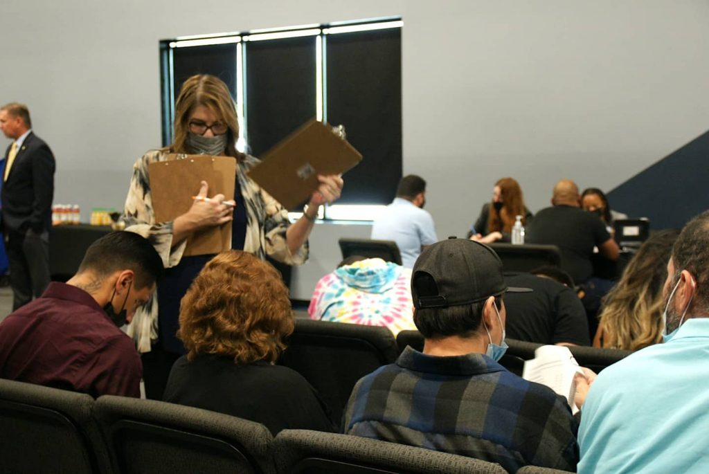 People are shown from the back seated on chairs, filling out forms as they wait to meet with San Bernardino County Public Defenders.