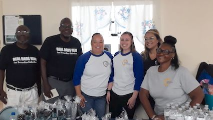 A group of six representatives from San Bernardino Fatherhood and the San Bernardino County Public Defender's Office stand smiling behind a table lined with giveaways.