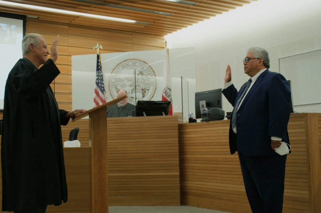 Judge John Pacheco, standing on left, swears in Judge Kawika Smith, right, at the San Bernardino Justice Center.