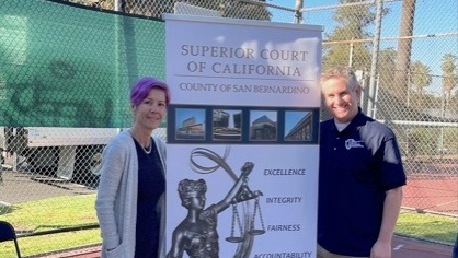 Public Defenders Lisa Slade (left) and Daniel Edber stand on either side of a banner for the Superior Court.
